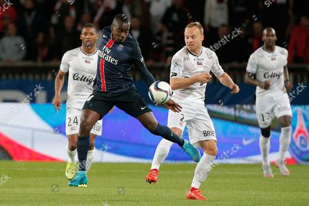 PSG's Blaise Matuidi, left, challenges for the ball with Guingamp's Lars Jacobsen, during the French League One soccer match between Paris Saint Germain and Guingamp, at the Parc des Princes stadium in Paris, France