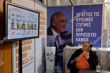 A supporter of New Democracy main opposition party watches the first exit polls at the electoral stand of the party in Athens, . Exit polls in Greece's early election show the left-wing Syriza party of former prime minister Alexis Tsipras likely winning, but falling short of an absolute majority needed to form a government. The banner next to the photograph of party's leader Vangelis Meimarakis reads in Greek ''In this crucial hour, everyone is needed