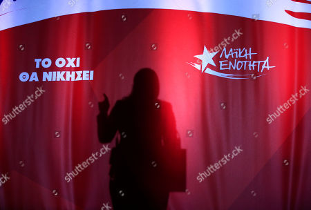 The shadow of former speaker of Greek Parliament and candidate with the newly-formed left-wing Popular Unity party Zoe Konstantopoulou is cast on the wall during her speech at a pre-election rally, in central Athens, . The party broke away from the governing Syriza party ahead of the Sept. 20 general election, hurting its re-election effort. The signs read in Greek: 'No will win', left and 'Publich Unity', right