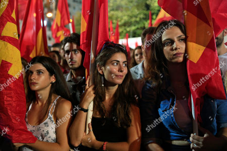 Supporters of Greece's Communist Party watch the party's leader Dimitris Koutsoumpas, delivering his speech, during a pre-election rally in central Athens, . Greece's goes to snap general election on Sept. 20, 2015. It is the third time this year Greeks will be voting, with the economy still in dire straits, a quarter of workers jobless, and capital controls limiting cash access to savings to 420 euros ($470) per week