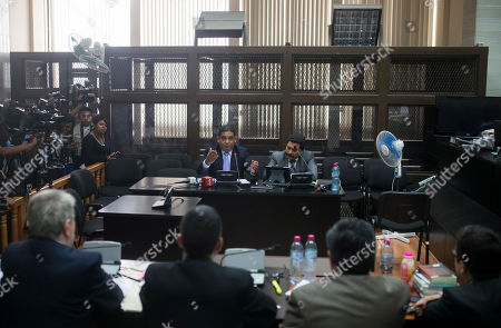 """Juan Carlos Monzon, Francisco Garcia Gudiel Juan Carlos Monzon, center left, the personal secretary of former Vice President Roxana Baldetti, speaks during a court hearing after he turned himself into authorities in Guatemala City, . Monzon is accused by authorities of being the head of a corruption ring, known as """"La Linea,"""" in which businesses allegedly paid kickbacks to government officials in exchange for lower import duties. It is believed that the scheme bilked the government of millions of dollars. The corruption scandal has rocked the Guatemalan government and so far has caused former President Otto Perez Molina and Baldetti to resign. Both are jailed and are facing charges for allegedly receiving the illegal payments. Prosecutors and an international commission have said Perez Molina and Baldetti were fully aware of the scheme and received half of the kickbacks paid. At right is Monzon's lawyer, Francisco Garcia Gudiel"""