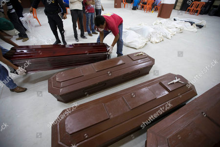 Volunteers arrange coffins at a provisional morgue in Santa Catarina Pinula, Guatemala, . The hill that towers over the Santa Catarina Pinula neighborhood known as Cambray, collapsed late Thursday after heavy rains, burying several houses with dirt, mud and rocks. Family members have reported 100 people missing, but the number could be as high as 600 based on at least 100 homes in the area of the slide, said Alejandro Maldonado, executive secretary of Conred, the country's emergency disaster agency