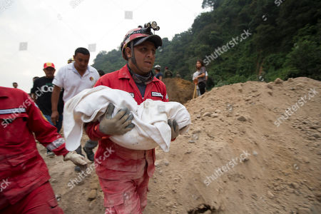 A fireman carries the body of a child recovered from the site of a landslide in Cambray, a neighborhood in the suburb of Santa Catarina Pinula, about 10 miles east of Guatemala City, . The hill that towers over Cambray collapsed late Thursday after heavy rains, burying several houses with dirt, mud and rocks. Family members have reported 100 people missing, but the number could be as high as 600 based on at least 100 homes in the area of the slide, said Alejandro Maldonado, executive secretary of Conred, the country's emergency disaster agency