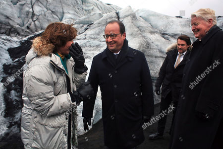 France's President Francois Hollande, center, shares a laugh with Iceland's First Lady, Dorrit Moussaieff, left, and Iceland's President Olafur Ragnar Grimsson, right, during a walk on the Solheimajokull glacier, where the ice has retreated by more than 1 kilometer (0.6 miles), during a State visit in Iceland, . Francois Hollande is in Iceland to experience firsthand the damage caused by global warming, ahead of major U.N. talks on climate change in Paris this year