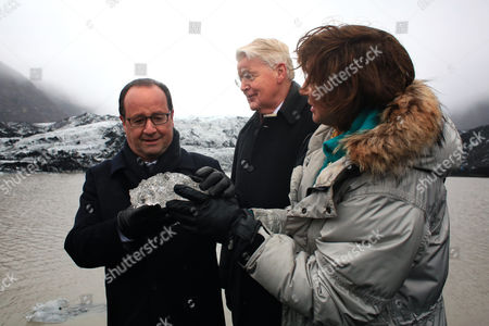 Iceland's First Lady, Dorrit Moussaieff, right, gives a block of ice to France's President Francois Hollande, left, as Iceland's President Olafur Ragnar Grimsson, center, looks, during a walk on the Solheimajokull glacier, where the ice has retreated by more than 1 kilometer (0.6 miles), during a State visit in Iceland, . Francois Hollande is in Iceland to experience firsthand the damage caused by global warming, ahead of major U.N. talks on climate change in Paris this year
