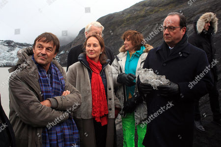 France's President Francois Hollande, right, holding a block of ice, and from let, French Environmentalist Nicolas Hulot, Environment Minister Segolene Royal, Iceland's President Olafur Ragnar Grimsson, and Iceland's First Lady, Dorrit Moussaieff, listen to a scientist on the Solheimajokull glacier, where the ice has retreated by more than 1 kilometer (0.6 miles), during a State visit in Iceland, . Francois Hollande is in Iceland to experience firsthand the damage caused by global warming, ahead of major U.N. talks on climate change in Paris this year