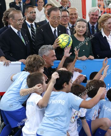 """UN Secretary-General Ban Ki-moon, flanked by his wife Yoo Soon-taek, right, and Italian soccer legend Roberto Baggio, bottom center, holds a soccer ball at the Expo World's Fair on the occasion of the UN World Food Day in Rho, near Milan, Italy, . Ban on Friday called for """"food security for all the people around the world, to build a global movement to end hunger"""
