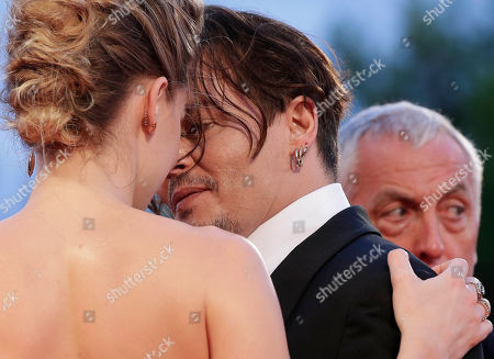 Stock Image of Johnny Depp, Amber Heard, Jerry Judge Johnny Depp, left, and Amber Heard pose for photographers, as Depp personal security guard Jerry Judge, right, looks on at the premiere of the film The Danish Girl during the 72nd edition of the Venice Film Festival in Venice, Italy, . The 72nd edition of the festival runs until Sept. 12