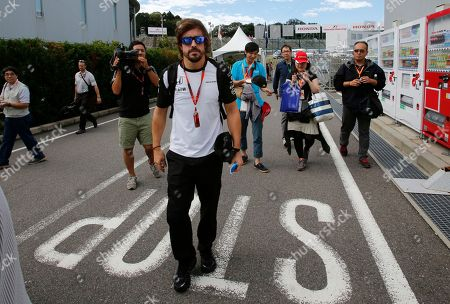 Jenson Button, Jessica Michibata McLaren driver Fernando Alonso of Spain walks at the paddock of the Suzuka Circuit ahead of the Japanese Formula One Grand Prix in Suzuka, central Japan