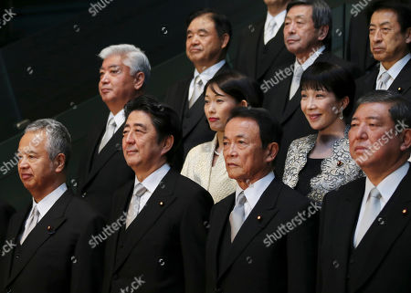 Japanese Prime Minister Shinzo Abe, second left at bottom row, and his new Cabinet members, pose for a group photo session at the prime minister's official residence, in Tokyo, . Prime Minister Abe reshuffled his Cabinet on Wednesday to focus on reviving the world's No. 3 economy. Cabinet members are from left at bottom, Minister in charge of Economic Revitalization Akira Amari, Abe, Minister of Finance Taro Aso, and Minister for Vitalizing Local Economy in Japan Shigeru Ishiba. From left in the middle row: Defense Minister Gen Nakatani, Minister of the Environment Tamayo Marukawa, and Internal Affairs Minister Sanae Takaichi. From left at top row: Olympics Minister Toshiaki Endo, Minister of Economy, Trade and Industry Motoo Hayashi, and Minister of Health, Labour and Welfare Yasuhisa Shiozaki