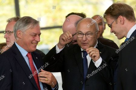 Stock Photo of French Finance Minister Michel Sapin, center, speaks with Governor of the Central Bank of France Christian Noyer, left, prior to a group photo of EU finance ministers at the European Council building in Luxembourg on . European Union finance ministers and central bankers hold informal talks to discuss taxation and ways to further deepen cooperation on the EU's euro single currency