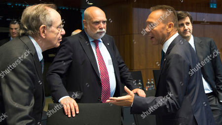 Governor of the Central Bank of Greece Yannis Stournaras, right, speaks with Italian Finance Minister Pier Carlo Padoan, left, during a meeting of EU finance ministers at the European Council building in Luxembourg on . European Union finance ministers and central bankers hold informal talks to discuss taxation and ways to further deepen cooperation on the EU's euro single currency