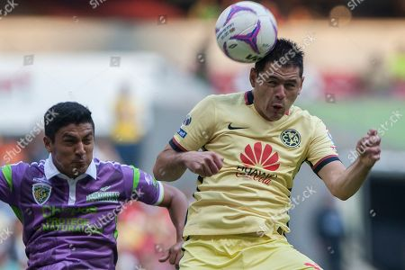 Pablo Aguilar, Luis Venegas America's Pablo Aguilar heads for the ball as Jaguares´ Luis Venegas looks on during a Mexican soccer league match in Mexico City