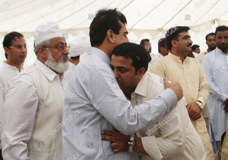 A man comforts Pakistan's former Prime Minister Yousuf Raza Gillani, third from left, who lost his nephew in a crush during the Hajj pilgrimage in Saudi Arabia, in Multan, Pakistan. As the hajj religious pilgrims entered its final day Saturday, officials in Saudi Arabia continued to grapple with the aftermath of a deadly stampede that killed at least 719 people