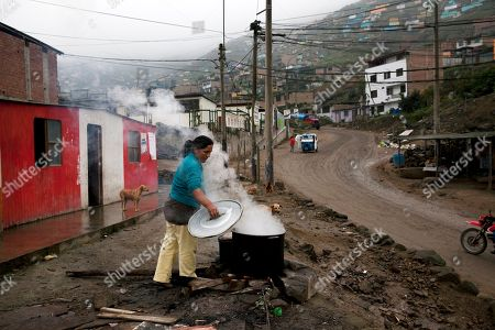 Lucia Mendez, 40, checks on a pot of frying fish, as she prepares lunches that she sells for 3.50 soles, or about one US dollar, in the Nueva Esperanza neighborhood, on the outskirts of Lima, Peru, . The annual meetings of the World Bank Group and the International Monetary Fund are taking place in Peru on Oct. 6-11, a country that according to the World Bank, has been able to reduce its poverty rate by more than half since 2002. Yet while only one in four Peruvians is poor, 40 percent of the population, or 12 million people, are at risk of sliding back into poverty