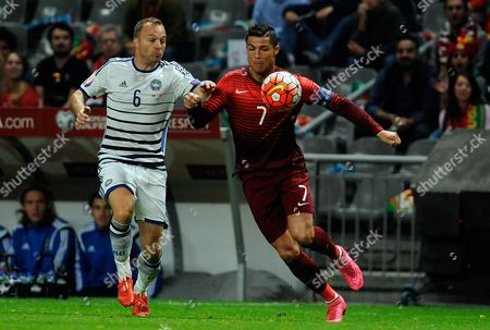 Portugal's Cristiano Ronaldo, right, fights for the ball with Denmark's Lars Jacobsen during the Euro 2016 qualifying group I soccer match between Portugal and Denmark at the Municipal Stadium in Braga, Portugal