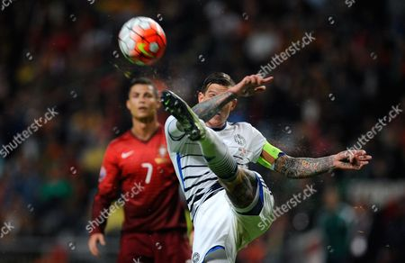 Denmark's Daniel Agger clears the ball away while Portugal's Cristiano Ronaldo looks on in the background during the Euro 2016 qualifying group I soccer match between Portugal and Denmark at the Municipal Stadium in Braga, Portugal
