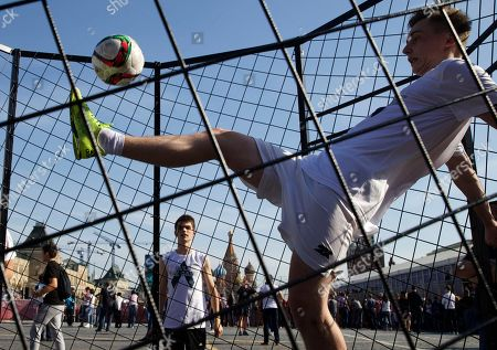 Young people play soccer in Red Square, with St. Basil Cathedral and Kremlin's Spassky Tower at left back, after the ceremony marking 1,000 days to the 2018 World Cup in Moscow, Russia, . Russia marked 1,000 days to go until the 2018 World Cup on Friday, but FIFA Secretary General Jerome Valcke was absent after being suspended from his duties