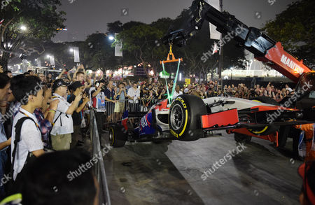 Spectator's watch as track marshals shift Manor driver Will Stevens of Britain's car after he crashed during the second practice session at the Singapore Formula One Grand Prix on the Marina Bay City Circuit in Singapore