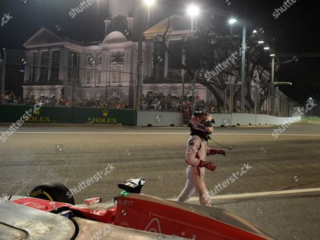 Manor driver Will Stevens of Britain walks from his car after crashing during the second practice session at the Singapore Formula One Grand Prix on the Marina Bay City Circuit in Singapore