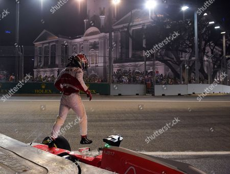 Manor driver Will Stevens of Britain jumps from his car after crashing during the second practice session at the Singapore Formula One Grand Prix on the Marina Bay City Circuit in Singapore