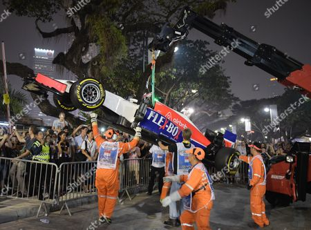 Track marshals shif Manor driver Will Stevens of Britain's car after crashing during the second practice session at the Singapore Formula One Grand Prix on the Marina Bay City Circuit in Singapore