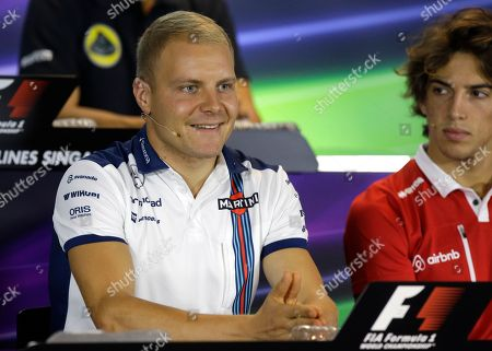 Williams driver Valtteri Bottas, left, of Finland answers a question as Manor driver Roberto Merhi of Spain watches during the driver's press conference at the Marina Bay City Circuit ahead of the Singapore Formula One Grand Prix in Singapore