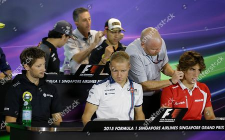 Manor driver Roberto Merhi, right, of Spain has a microphone fitted at the driver's press conference at the Marina Bay City Circuit ahead of the Singapore Formula One Grand Prix in Singapore, . Lotus driver Romain Grosjean of France, Force India driver Sergio Perez of Mexico, Williams driver Valtteri Bottas of Finland and Lotus driver Pastor Maldonado of Venezuela also prepare for the conference