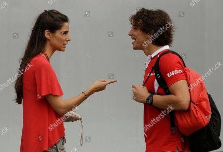Manor driver Roberto Merhi of Spain chats with a friend on his arrival at the Marina Bay City Circuit ahead of the first practice session at the Singapore Formula One Grand Prix