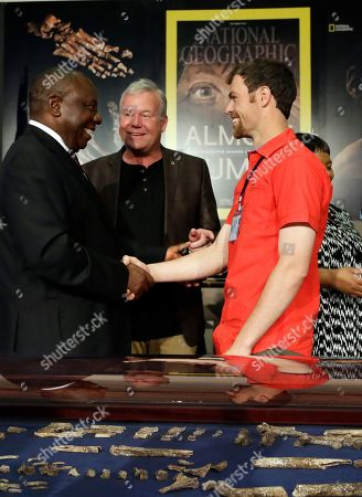 South Africa Deputy President Cyril Ramaphosa, left, shakes hand whislt introduced to Steven Tucker, right, by Lee Berger, a professor at the University of the Witwatersrand, center, at the Maropeng Cradle of Humankind in Magaliesburg, South Africa, . It was the night of Sept. 13, 2013, and Tucker and his caving partner had just discovered the remains of what scientists would determine to be a new member of the human family tree