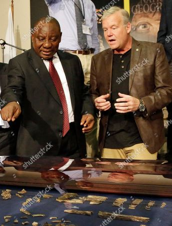 Lee Berger, a professor at the University of the Witwatersrand, right, presents to South Africa Deputy President Cyril Ramaphosa, right, the of the hundreds of other fossil elements recovered from a cave during the announcement at Maropeng Cradle of Humankind in Magaliesburg, South Africa . Scientists say they've discovered a new member of the human family tree, revealed by a huge trove of bones in a barely accessible, pitch-dark chamber of a cave in South Africa