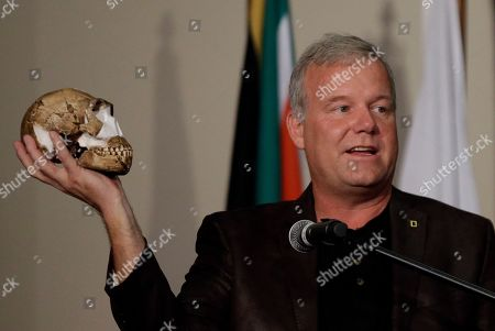 Stock Picture of Lee Berger, a professor at the University of the Witwatersrand, holds a reconstruction of the skull of Homo naledi at Magaliesburg, South Africa, . Scientists say they've discovered a new member of the human family tree, revealed by a huge trove of bones in a barely accessible, pitch-dark chamber of a cave in South Africa, showing a surprising mix of human-like and more primitive characteristics