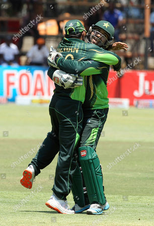 Pakistan player Muhammad Rizwan, left, celebrates with teammate Sarfraz Ahmed after taking a catch during the One Day International Cricket match between Zimbabwe and Pakistan, in Harare