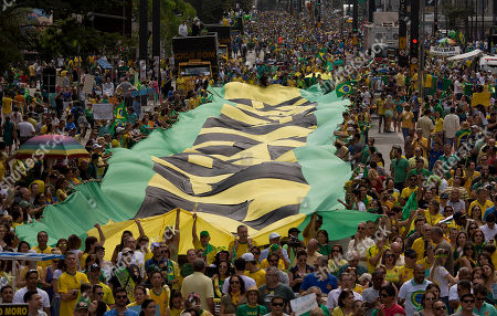 """Demonstrators shout anti-government slogans as they march holding a giant flag with the word """"Impeachment"""" written on it, during a protest demanding the impeachment of Brazil's President Dilma Rousseff in Sao Paulo, Brazil, . Demonstrations are taking place across Brazil against President Rousseff, whose popularity has never been lower as she faces a sputtering economy and a massive corruption scandal"""