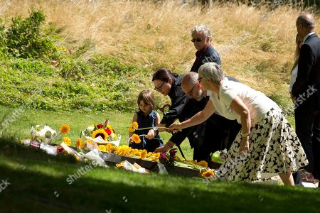 Australia's Gill Hicks, second left, who lost both her legs, lays a flower flanked by her daughter Amelie, left, during a service for survivors and relatives of the victims to mark the 10 year anniversary of the 7/7 London attacks, at the 7/7 memorial in Hyde Park, London, as Britons paused in silence and walked in solidarity Tuesday to mark the 10th anniversary of suicide bomb attacks on London's transit system. Four British men inspired by al-Qaida blew themselves up on three London subway trains and a bus during the morning rush hour on July 7, 2005, killing 52 commuters and injuring more than 700