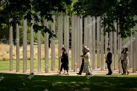 Australia's Gill Hicks, left, who lost both her legs, walks to lay a flower during a service for survivors and relatives of the victims to mark the 10 year anniversary of the 7/7 London attacks, at the 7/7 memorial in Hyde Park, London, as Britons paused in silence and walked in solidarity Tuesday to mark the 10th anniversary of suicide bomb attacks on London's transit system. Four British men inspired by al-Qaida blew themselves up on three London subway trains and a bus during the morning rush hour on July 7, 2005, killing 52 commuters and injuring more than 700