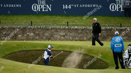 United States' Billy Horschel plays out of a bunker on hole 17 as United States' Mark Calcavecchia, back right, looks on during a practice round at the British Open Golf Championship at the Old Course, St. Andrews, Scotland