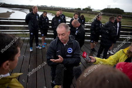 Brighton and Hove Albion Football Club Head Groundsman Steve Winterburn speaks to the media after he and the club's ground staff, standing behind him, laid a shirt and flowers in memory of their ground staff colleague Matt Grimstone, who was a keen amateur soccer goalkeeper traveling in a vehicle to play in a match with his teammate Jacob Schilt, alongside other tributes on a footbridge for people killed when a Hawker Hunter jet crashed into a highway Saturday after it failed to pull out of a loop maneuver during the Shoreham Airshow, near Shoreham, England, about 75 kilometers (45 miles) south of London, . Police said the death toll in the crash will probably rise as emergency workers probe wreckage on the freeway where the plane went down, plowing through cars on the road and exploding in a huge fireball