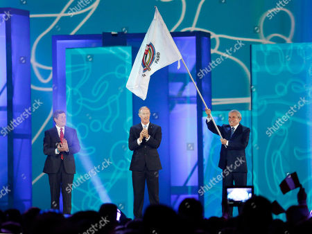 Ivar Sisniega, Luis Castaneda Lossio, John Tory Luis Castaneda Lossio, right, the mayor of Lima, Peru, waves the Pan American Sports Organization flag after it was handed over to him by Ivar Sisniega, center, the vice president of the PASO, during the closing ceremony of the Pan Am Games, in Toronto. Lima will be the host city for the 2019 Pan Am Games. At left is John Tory, the mayor of Toronto