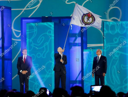 Stock Image of Ivar Sisniega, Luis Castaneda Lossio, John Tory Ivar Sisniega, center, the vice president of the Pan American Sports Organization, waves the PASO flag before handing it over to Luis Castaneda Lossio, right, the mayor of Lima, Peru, during the closing ceremony of the Pan Am Games, in Toronto. Lima will be the host city for the 2019 Pan Am Games. At left is John Tory, the mayor of Toronto