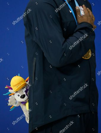 Giles Smith United States' Giles Smith holds Pachi doll during the medal ceremony after winning the gold medal in the the men's 100m butterfly final at the Pan Am Games, in Toronto