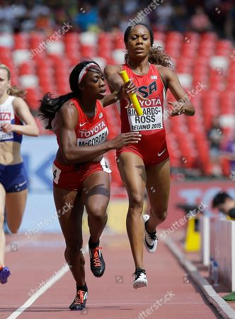 United State's Sanya Richards-Ross, right, hands the baton to Francena McCorory in the women's 4x400m relay round one at the World Athletics Championships at the Bird's Nest stadium in Beijing