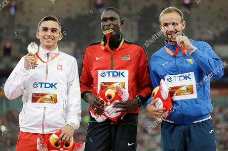 Men's 800m gold medal winner Kenya's David Rudisha, centre, stands with silver medalist Poland's Adam Kszczot, left, and bronze medalist Bosnia's Amel Tuka during the medal ceremony at the World Athletics Championships at the Bird's Nest stadium in Beijing