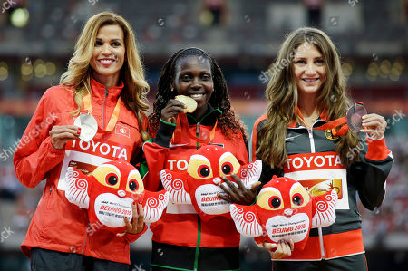 Women's 3000m steeplechase gold medalist Kenya's Hyvin Jepkemoi, centre, stands with silver medalist Tunisia's Habiba Ghribi, left, and bronze medalist Germany's Gesa Krause on the podium at the World Athletics Championships at the Bird's Nest stadium in Beijing