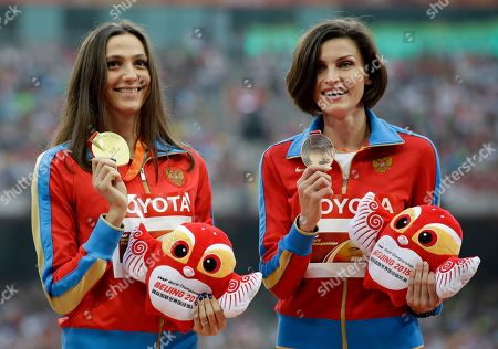 Women's high jump gold medalist Russia's Maria Kuchina, centre, stands with compatriot and bronze medalist Anna Chicherova on the podium at the World Athletics Championships at the Bird's Nest stadium in Beijing