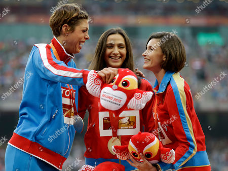 Women's high jump gold medalist Russia's Maria Kuchina, centre, stands with silver medalist Croatia's Blanka Vlasic, left, and compatriot and bronze medalist Anna Chicherova as they celebrate on the podium at the World Athletics Championships at the Bird's Nest stadium in Beijing