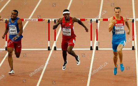 Philippines's Eric Cray, United States' Bershawn Jackson and Russia's Ivan Shablyuyev, from left, compete in a men's 400m hurdles heat during the World Athletics Championships at the Bird's Nest stadium in Beijing