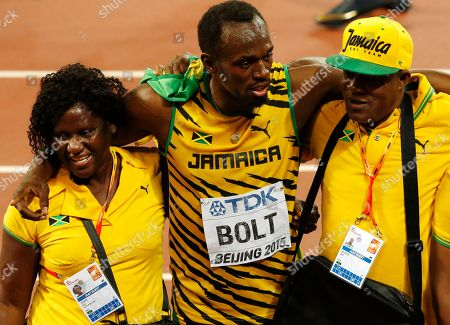 Jamaica's Usain Bolt celebrates with his mother Jennifer Bolt, left, and his father Wellesley Bolt after winning the gold medal in the men's 100m final during the World Athletics Championships at the Bird's Nest stadium in Beijing