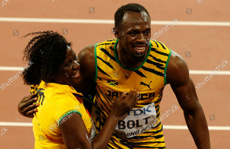 Jamaica's Usain Bolt celebrates with his mother Jennifer Bolt, left, after winning the gold medal in the men's 100m final during the World Athletics Championships at the Bird's Nest stadium in Beijing