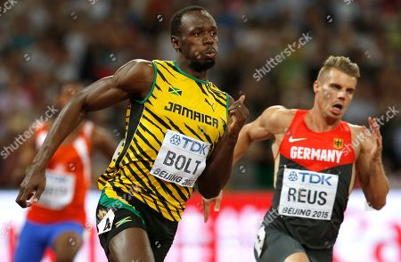 Jamaica's Usain Bolt and Germany's Julian Reus competes in a men's 200m round one heat at the World Athletics Championships at the Bird's Nest stadium in Beijing